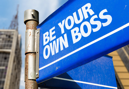 Be your own boss signpost on building background