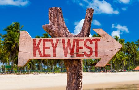 key west: Key West sign with arrow on beach background