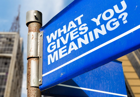 What gives you meaning? signpost on building background Stock Photo