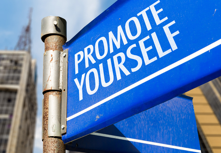 promote: Promote yourself signpost on building background Stock Photo