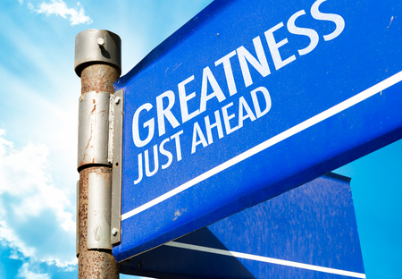 greatness: Greatness just ahead signpost on sky background