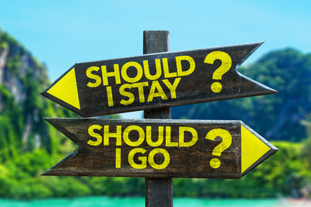 Should I stay?Should I go? sign with wetland background