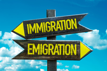 emigranti: Text sign with arrow on clouds and sky background: Immigrationemigration
