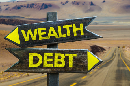 deficit target: Wealthdebt sign with arrow on desert background Stock Photo