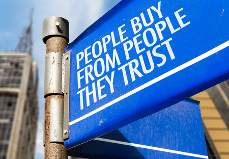 trust people: People buy from people they trust signpost on building background Stock Photo