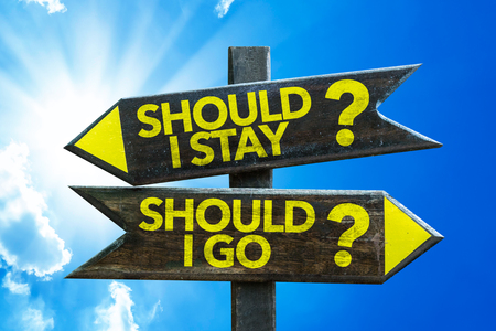indecisiveness: Should I stay?Should I go? sign with arrow on sunny background