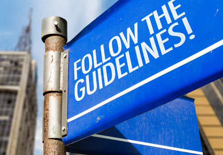 principles: Follow the guidelines! signpost on building background Stock Photo