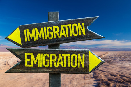 emigranti: Immigrationemigration sign with arrow on desert background Archivio Fotografico