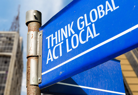 Think global act local signpost on building background Stock fotó