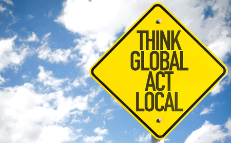 Think global act local sign with clouds and sky background Standard-Bild