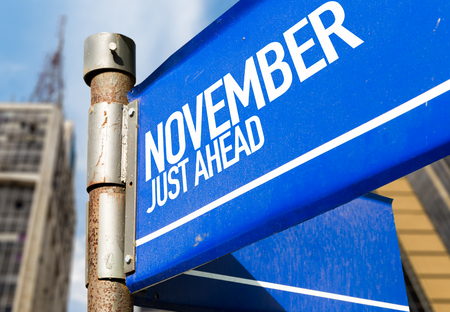 building planners: November just ahead signpost on building background