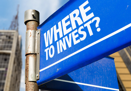 Where to invest? signpost on building background Stock Photo