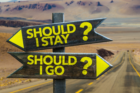 indecisiveness: Should I stay?Should I go? sign with arrow on desert background