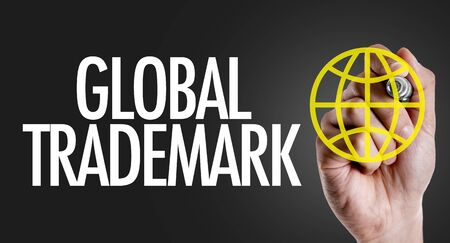 Hand holding a marker with Global Trademark