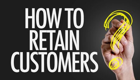 Hand holding a marker with How to retain customers concept Stock Photo