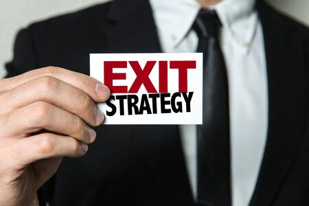 Businessman showing a card with the words Exit Strategy Stock Photo