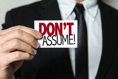 Empresario mostrando una tarjeta con las palabras no asumas