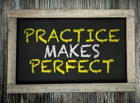 Practice Makes Perfect words on a blackboard Foto de archivo