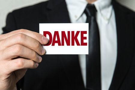 Businessman showing a card with the word Danke