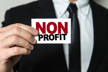 Businessman showing a card with the words Non Profit