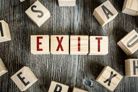 Wooden blocks on a table spelling the word exit