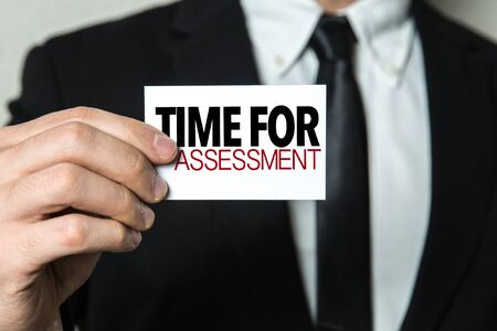 Man holding time for assessment card