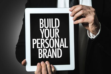 Man holding tablet with build your personal brand Stock fotó