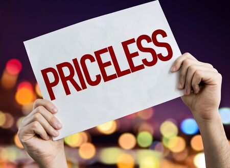 Hands holding Priceless placard with bokeh background Stock Photo