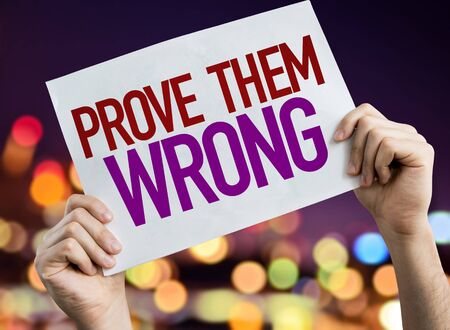 Hands holding Prove them wrong placard with bokeh background 版權商用圖片