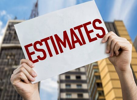 Hands holding Estimates placard with urban background
