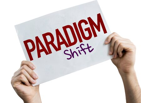 Hands holding Paradigm Shift placard with white background