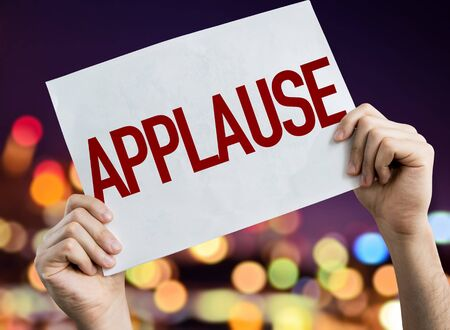 Mains tenant une pancarte d'applaudissements avec un arrière-plan flou Banque d'images