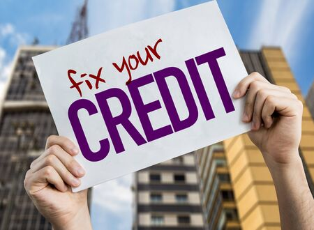 Hands holding Fix Your Credit placard with urban background