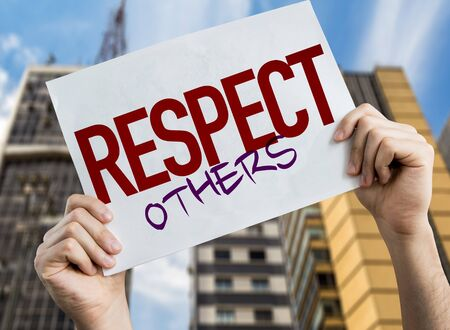 Hands holding Respect Others placard with urban background