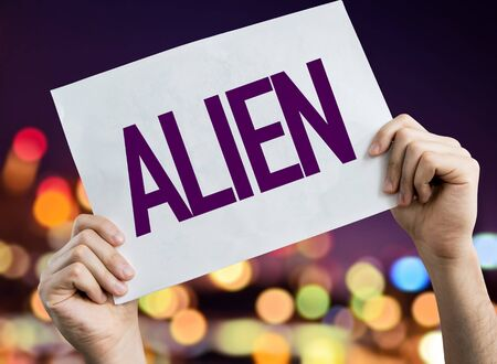 Person holding placard with the word Alien