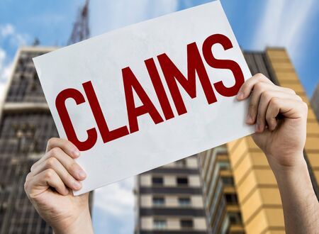 Person holding placard with the word Claims Banco de Imagens