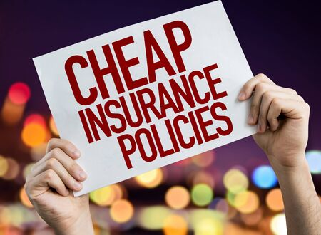 Person holding placard with the words Cheap Insurance Policies 版權商用圖片