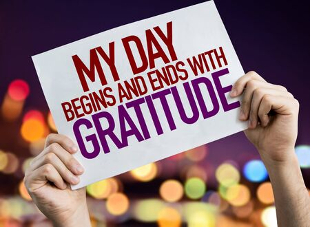 Person holding placard with the words My Day Begins And Ends With Gratitude Stock Photo