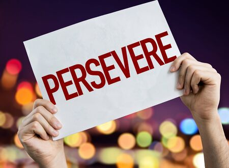 Person holding placard with the word Persevere