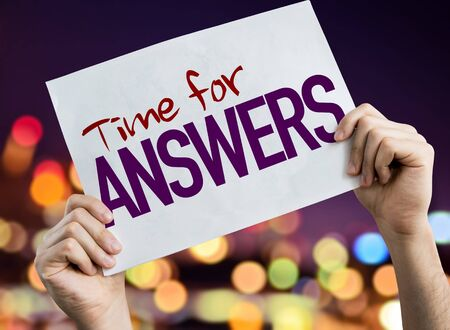 Person holding placard with the words Time For Answers 版權商用圖片