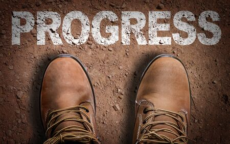 Boots on the trail with the word Progress Фото со стока - 129783670