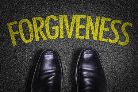 Business shoes on the floor with the word Forgiveness