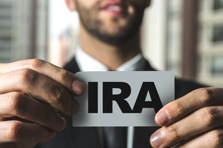 Person holding a card with IRA Stock Photo - 129784136