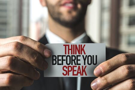 Person holding a card with Think Before You Speak