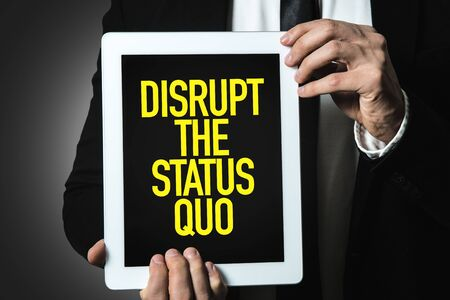 Person holding a tablet with Disrupt The Status Quo
