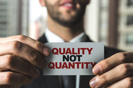 Person holding a card with Quality not Quantity