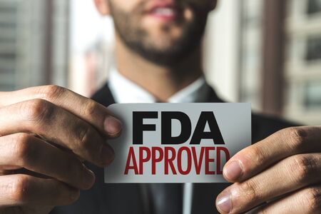 Person holding a card with FDA approved Stok Fotoğraf - 130036594