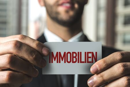 Person holding a card with Immobilien