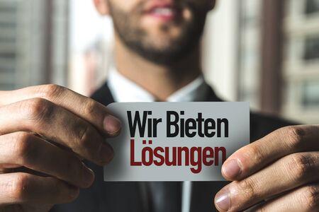 Person holding a card with Wir Bieten Losungen Zdjęcie Seryjne