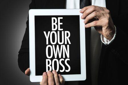 Personne tenant une tablette avec Be Your Own Boss